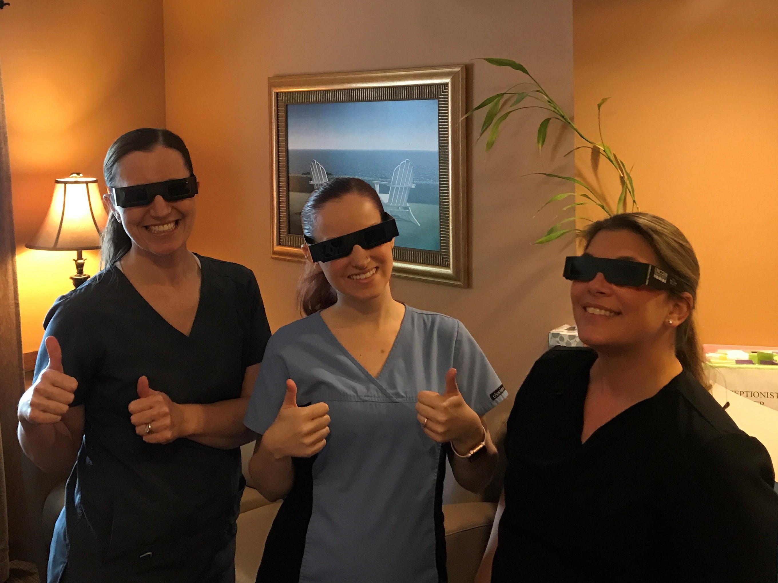 A picutre of Dr. Steckelber and staff wearing their solar glasses!